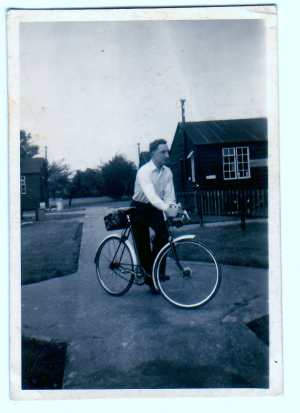 Man stood with a bicycle.